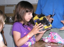 The young scientist opens her birthday gift.