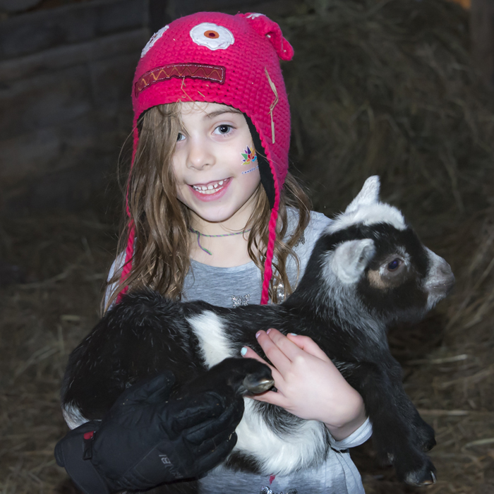 Lexi holding a baby goat. Great pic Grandpa Rick!